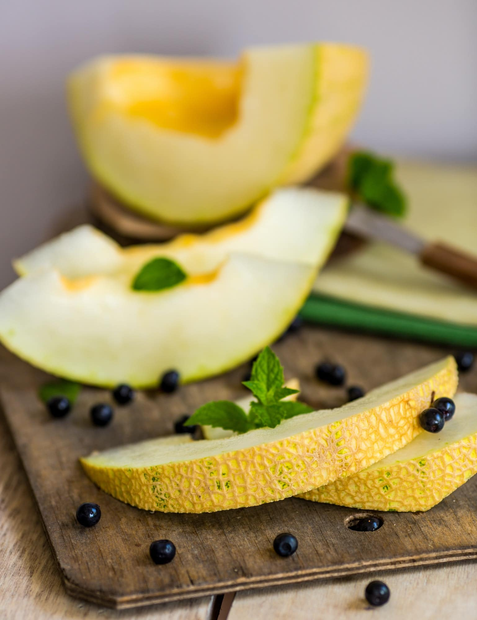 fresh melon and blueberries on a wooden cutting board. selective focus